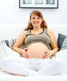 Pregnant woman sitting on sofa and touching belly Royalty Free Stock Image