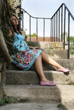 Pregnant woman sitting on the steps of private hou Royalty Free Stock Image