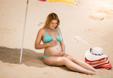 Pregnant woman sitting under parasol and talking to abdomen Royalty Free Stock Image