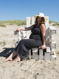 Pregnant woman sitting on wooden chair on the beac. Adult happy pregnant woman sitting on wooden chair on the beach Stock Images