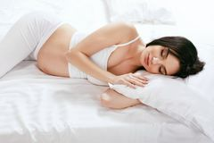Pregnant Woman Sleep. Girl Sleeping With Pillow On Bed. Pregnant Woman Sleep. Beautiful Girl Sleeping With Pillow On Bed In White Interior. High Resolution royalty free stock photography