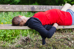 Pregnant woman sleeping on bench in forest Royalty Free Stock Photo