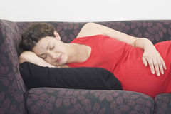 Pregnant Woman Sleeping On Sofa Stock Photo