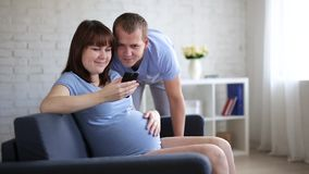 Pregnant woman with smartphone and her husband stock video