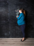 Pregnant woman smelling flowers drawn by chalk on big black wall Stock Photography