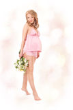 Pregnant woman smiling, looking at camera. Holding flowers, standing on tiptoe. Pink dress Royalty Free Stock Images