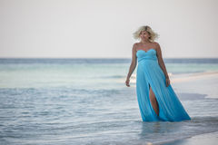 Pregnant woman is smiling and walking in the sea Stock Photo