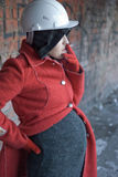 Pregnant woman smokes. Pregnant woman in red coat and helmet smokes a cigarette Royalty Free Stock Image