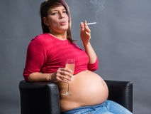 Pregnant woman smoking cigarette and drinking Alcohol. Stock Photo