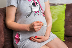 Pregnant woman smoking cigarette at home stock images