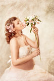 Pregnant woman sniffing flowers and dreaming. Sitting with closed eyes Stock Photos
