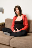 Pregnant woman on sofa Royalty Free Stock Photo