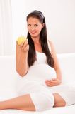 Pregnant woman on sofa eating an apple Royalty Free Stock Photography