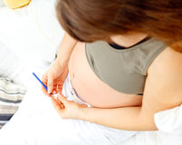 Pregnant woman on sofa knitting for her baby Royalty Free Stock Image