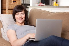 Pregnant Woman on Sofa with Laptop Royalty Free Stock Photos