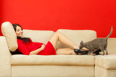 Pregnant woman on sofa playing with cat Stock Photography