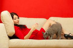 Pregnant woman on sofa playing with cat Stock Photos