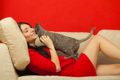 Pregnant woman on sofa playing with cat Stock Image