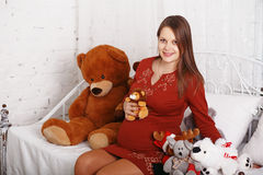 Pregnant woman with soft toys Stock Images