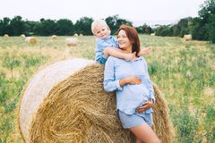 Pregnant woman and son on nature. Mother waiting of a second bab Stock Photos