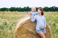 Pregnant woman and son on nature. Mother waiting of a second bab. Beautiful pregnant women and her cute toddler son having fun on wheat field with haystacks at Royalty Free Stock Photos