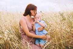 Pregnant woman and son on nature. Mother waiting of a second bab. Beautiful pregnant women and her cute toddler son having fun on wheat field with haystacks at Stock Images