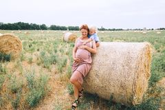 Pregnant woman and son on nature. Mother waiting of a second bab. Beautiful pregnant women and her cute toddler son having fun on wheat field with haystacks at Stock Photo
