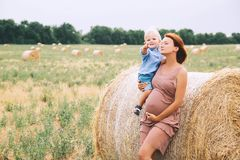 Pregnant woman and son on nature. Mother waiting of a second bab. Beautiful pregnant women and her cute toddler son having fun on wheat field with haystacks at Royalty Free Stock Images