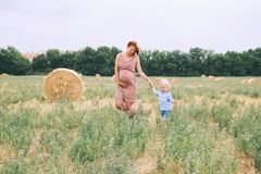 Pregnant woman and son on nature. Mother waiting of a second bab Stock Image