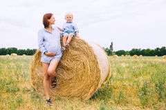Pregnant woman and son on nature. Mother waiting of a second bab. Beautiful pregnant women and her cute toddler son having fun on wheat field with haystacks at Stock Photos