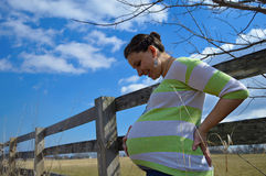 Pregnant Woman with Split Rail Fence. A beautiful, overdue, expectant mother with rustic looking split rail fence in the background Stock Image