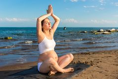 Pregnant woman in sports bra doing exercise in relaxation on yoga pose Stock Photos