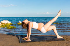 Pregnant woman in sports bra doing exercise in relaxation on yoga pose Royalty Free Stock Photos