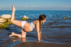 Pregnant woman in sports bra doing exercise in relaxation on yoga pose on sea Royalty Free Stock Photos