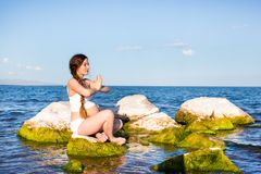 Pregnant woman in sports bra doing exercise in relaxation on yoga pose on sea. Royalty Free Stock Image