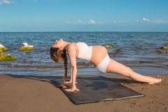 Pregnant woman in sports bra doing exercise on yoga pose on sea Stock Photography