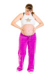 Pregnant woman in sportswear holding her tummy Stock Photography