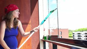 Pregnant woman is cleaning window at home balcony. Pregnant woman spray and wipe glass window at home balcony. Housework routine, cleaning and household concept stock footage