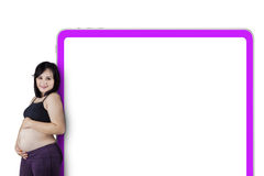 Pregnant woman standing with billboard Royalty Free Stock Photography
