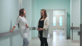 A pregnant woman standing in the corridor of the perinatal center communicates with a woman doctor in a white coat.  stock video footage