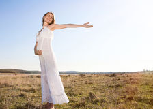 Pregnant woman standing on field Stock Photo