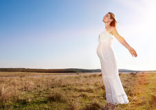 Pregnant woman standing on field Stock Image