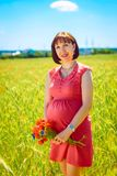 Pregnant woman standing in a field Royalty Free Stock Photo
