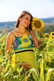 Pregnant woman standing on field sunflowers Stock Photography