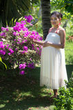 Pregnant woman standing with flower bushes Royalty Free Stock Photography
