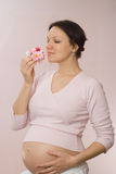 Pregnant woman standing and holding a flowers Royalty Free Stock Image