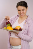 Pregnant woman standing and holding fruits Royalty Free Stock Photo