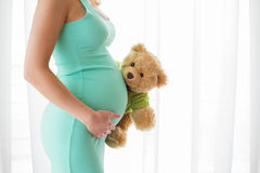 Pregnant woman standing and holding teddy bear toy. Pregnant woman standing and holding teddy bear royalty free stock photography