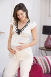 Pregnant woman standing in living room smiling Stock Photos