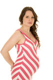 Pregnant woman standing looking in a red and white dress Royalty Free Stock Images